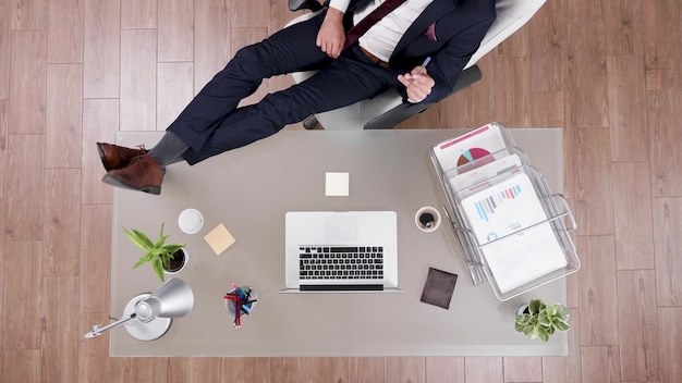 Top view of businessman in suit staying relaxed with feet on office desk analyzing financial graphs on laptop. executive manager working in startup company office at management investments