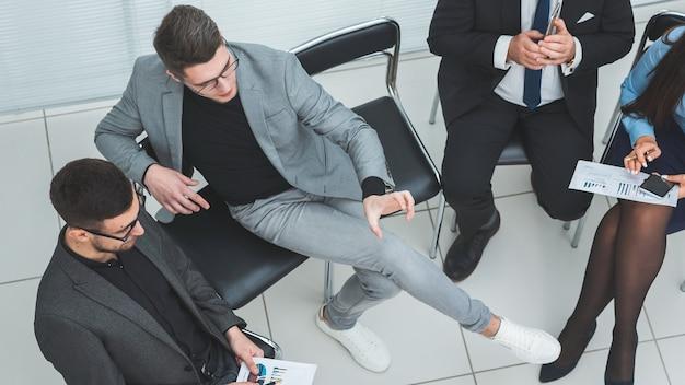 仕事の会議中にスマートフォンを使用してトップビューのビジネスマン