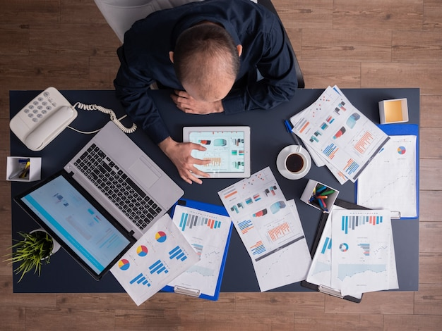 Top view of businessman using tablet pc analyzing financial charts and documents, sitting at desk in corporate office