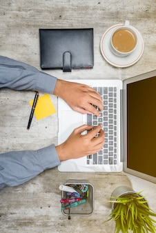 Top view of businessman working using laptop with coffee, potted plant, notebook, notes paper and business accessories