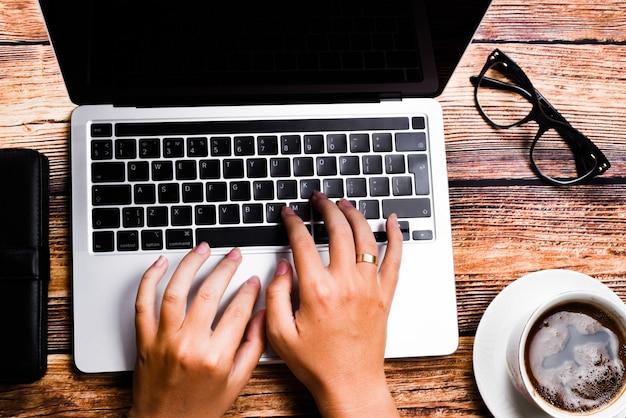 職場でノートパソコンに入力する平面図実業家。ホームオフィスの手キーボードで働く女性。職場のコンセプト