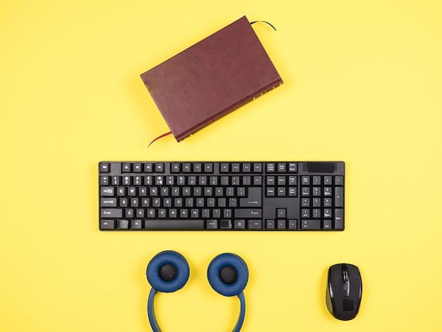 노란색 책상, 헤드폰, 책에 대한 상위 뷰 탈취 남자 개념 이미지