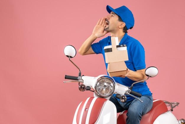 Vista dall'alto di un corriere impegnato che indossa un cappello seduto su uno scooter in possesso di ordini che chiama qualcuno su sfondo color pesca pastello