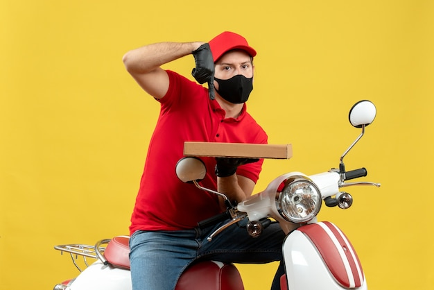Vista dall'alto del corriere impegnato uomo che indossa camicetta rossa e guanti cappello in maschera medica che si siede sull'ordine di puntamento scooter