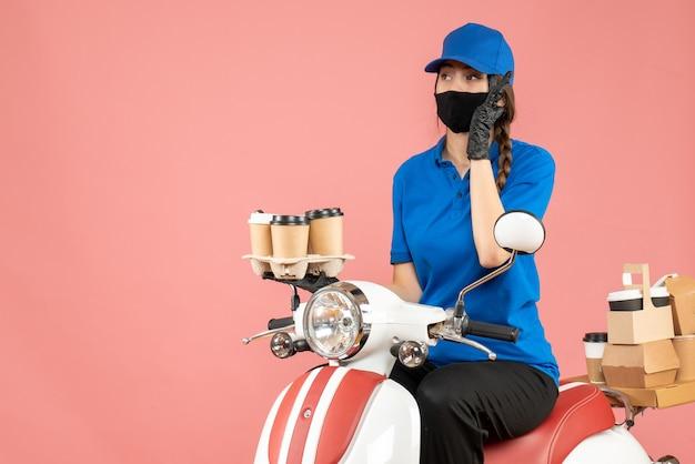 Vista dall'alto della donna del corriere impegnata che indossa maschera medica e guanti seduti su uno scooter che consegna ordini su sfondo color pesca pastello