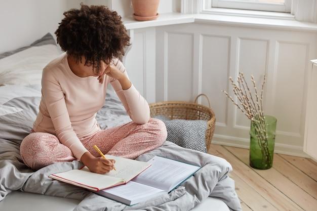 La vista superiore della donna dalla pelle scura occupata annota i record in taccuino dal libro