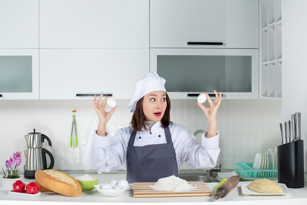 Top view of busy female chef in uniform standing behind the table with cutting board foods holding eggs in the white kitchen