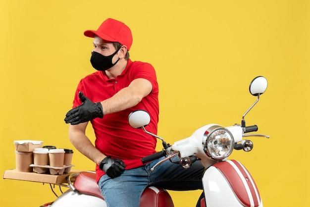 Vista superiore del giovane adulto occupato che indossa la camicetta rossa e guanti del cappello nella mascherina medica che trasporta l'ordine che si siede sullo scooter che dà il benvenuto a qualcuno