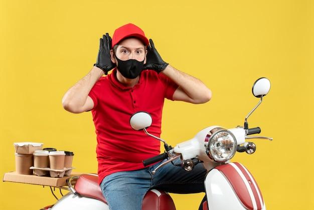 Vista superiore del giovane adulto occupato che indossa la camicetta rossa e guanti del cappello nella mascherina medica che trasporta l'ordine che si siede sul motorino