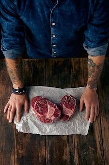 Vista dall'alto delle mani del macellaio e delle bistecche su carta artigianale
