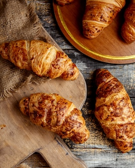 Top view of butter croissants placed on wooden board