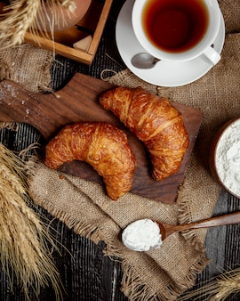 Top view of butter croissants places on wooden board