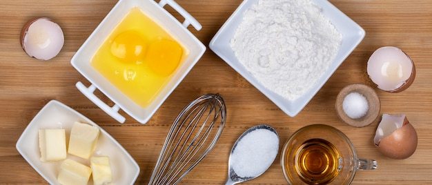 Top view on a butter, sugar, eggs, flour, salt and rome ingredients for cooking a cake