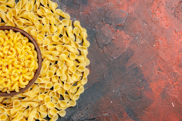 Top view of butterfly uncooked pastas in a brown bowl on the right side of mixed color background