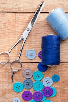 Top view of buttons with thread and scissors