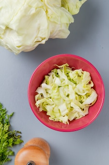 Top view of cabbage slices in bowl with whole one coriander and salt on blue background