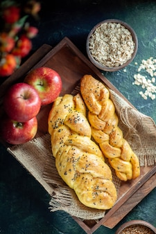 Top view cable-knit breadsticks apples on rectangle wood board oats bowl on table
