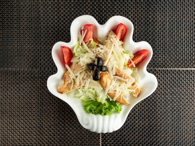Top view of caesar salad in hand shaped plate