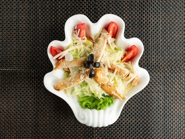 Top view of caesar salad served in hand-shaped plate
