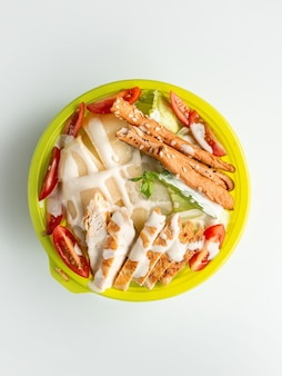 Top view of caesar salad with bread sticks in white background