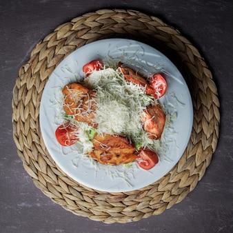Vista dall'alto insalata caesar con pollo, pomodoro, lattuga, olive, cracker, parmigiano in un piatto bianco su un supporto di vimini