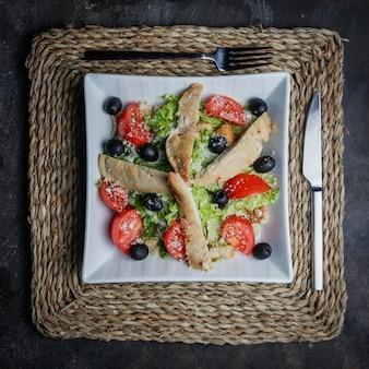 Vista dall'alto insalata caesar con pollo, pomodoro, lattuga, olive, cracker, parmigiano su un supporto di vimini in un piatto bianco