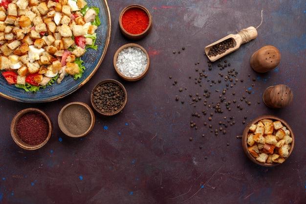 ダークデスクで調味料を変えたトップビューシーザーサラダサラダフードミールランチ野菜