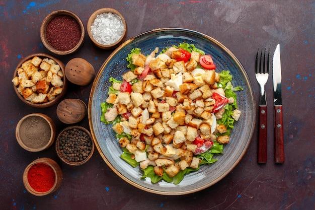暗い壁の野菜のプレートの内側にスライスした野菜とラスクを添えた上面シーザーサラダサラダ食品ランチ食事ラスク味