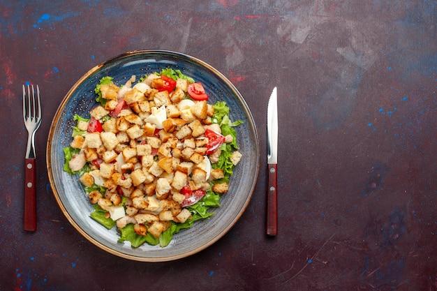 暗い床にスライスした野菜とラスクを添えた上面シーザーサラダ野菜サラダ食品ランチ食事ラスク味