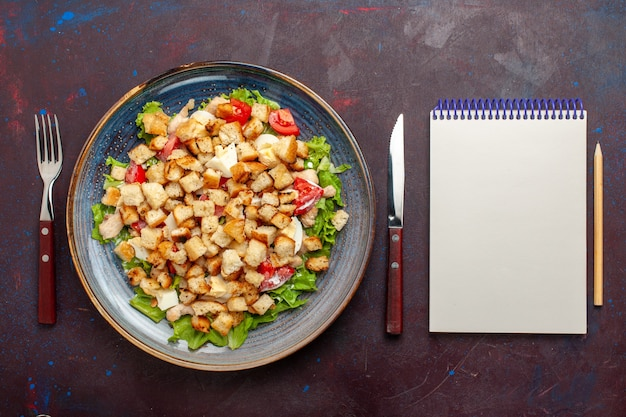 暗い壁にスライスした野菜とラスクを添えた上面シーザーサラダ野菜サラダ食品ランチ食事ラスク味の写真