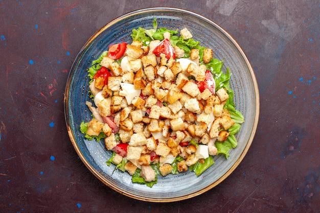 暗い壁にスライスした野菜とラスクを添えた上面シーザーサラダ野菜サラダ食品ランチ食事ラスク味