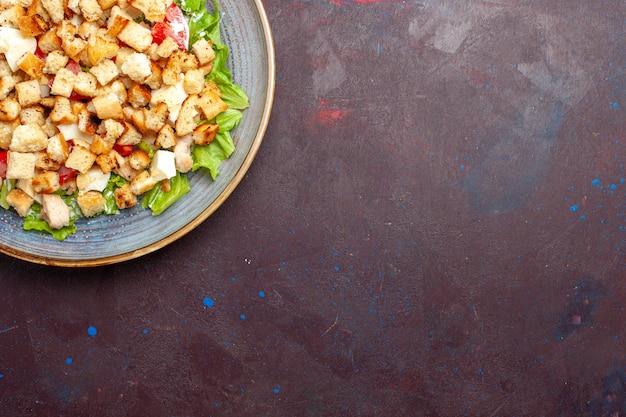 暗い壁にスライスした野菜とラスクを添えた上面シーザーサラダサラダ食品ランチミールラスク味
