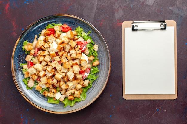 ダークデスクにスライスした野菜とラスクを添えたトップビューシーザーサラダ野菜サラダフードランチミールラスクテイスト