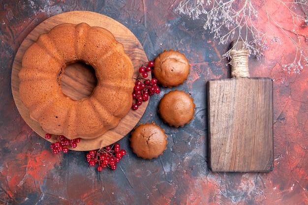 Vista dall'alto torta una torta con ribes rosso gli appetitosi cupcakes accanto al tagliere