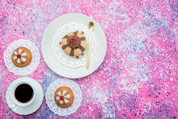 Top view cake and cookies along with cup of coffee on the colored background cookie cake color sugar