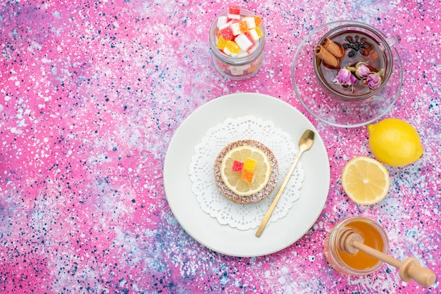 Вид сверху торт внутри тарелки с чаем лимонным мармеладом на цветном фоне цветной торт бисквитный сахар сладкий