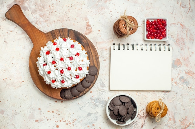 Top view cake on plate notebook bowls with berries and chocolate cookies tied with rope on light grey table