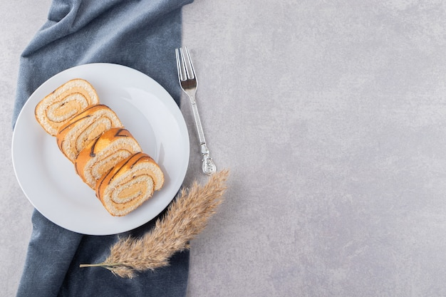 Top view of cake rolls on white plate over grey background.