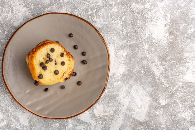 Top view of cake slice inside plate with choco chips on light surface