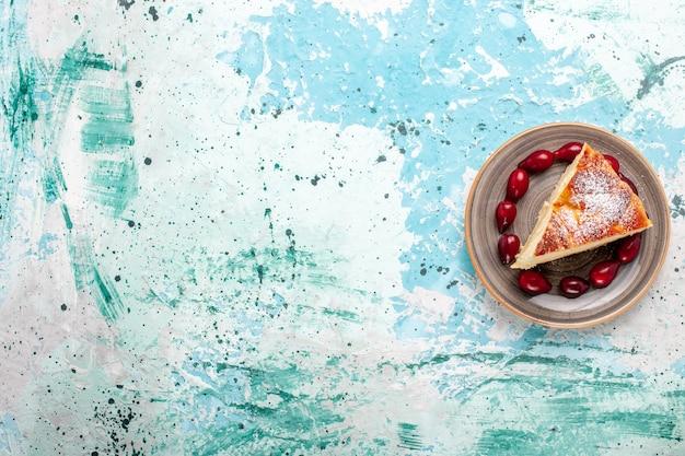 Вид сверху кусочек торта с свежими красными кизилами на голубом фоне фруктовый торт выпечка пирог сахарный бисквит сладкий