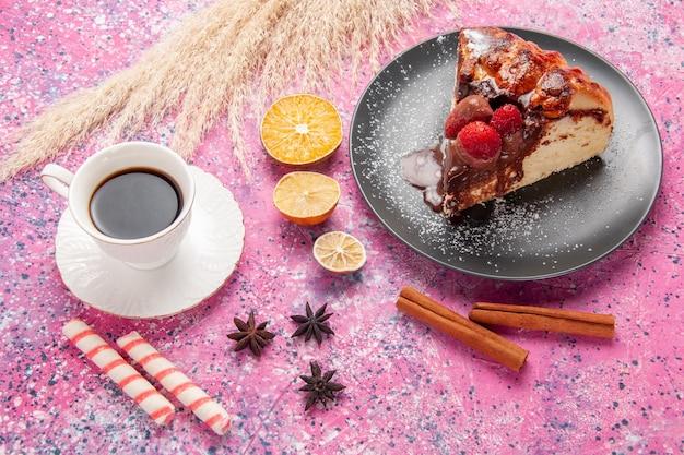 Вид сверху кусок торта с шоколадом и красной клубникой чашка чая на розовом столе печенье сладкий сахар десертный торт выпечка