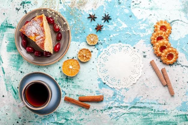Вид сверху на кусок торта с печеньем и чашкой чая на синей поверхности, фруктовый торт, выпечка, пирог, бисквит, сладкий