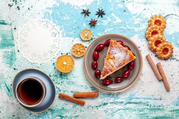 Fetta di torta vista dall'alto con biscotti e tazza di tè sulla torta di frutta blu scrivania cuocere il biscotto torta dolce