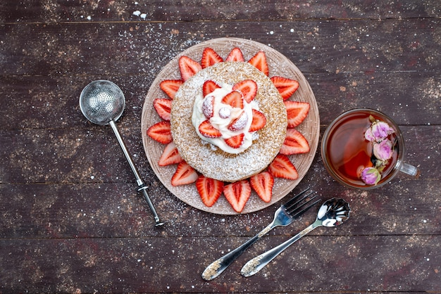 A top view cake slice with cream and fresh red strawberries inside plate with tea on the dark background