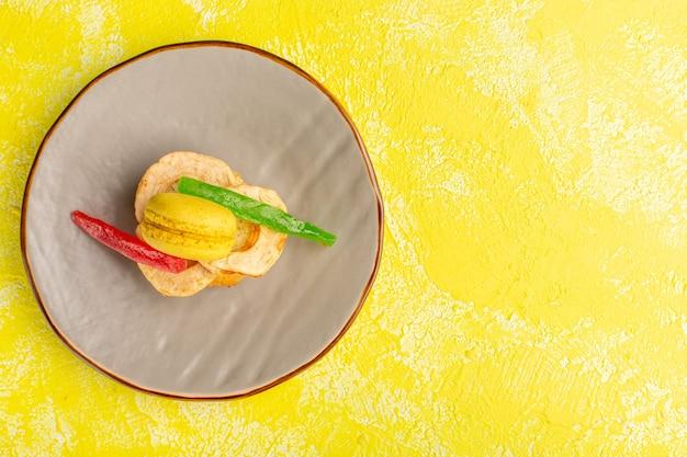 Vista dall'alto della fetta di torta con macaron e marmellata all'interno della piastra sulla superficie gialla