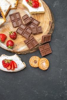 Кусочки торта с шоколадными батончиками и печеньем, вид сверху на сером столе