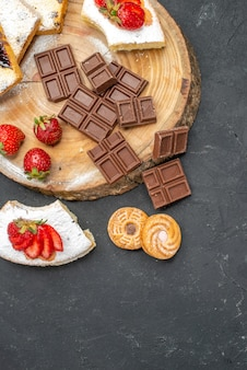 Fette di torta vista dall'alto con barrette di cioccolato e biscotti sulla scrivania grigia