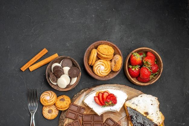 Вид сверху кусочками торта с печеньем и шоколадом на темном фоне