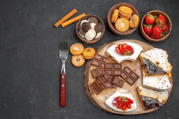 暗い机の上にクッキーとチョコレートとトップビューのケーキのスライス