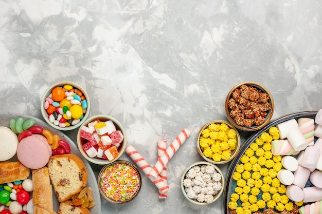 Top view of cake slices with french macarons bagels and candies on white wall